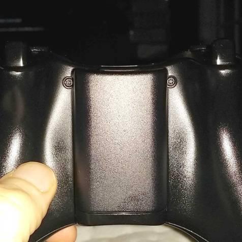 Nas laterais do compartimento de pilhas, note os parafusos do tipo Torx