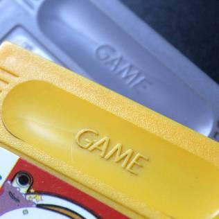"""Cartucho paralelo com a palavra """"GAME"""" gravada na frente"""