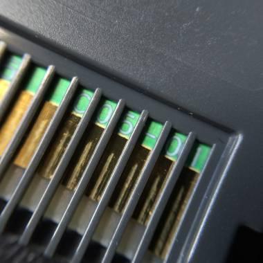 Código impresso no PCB é visível por entre as ranhuras do cartucho original
