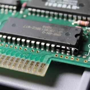 O PCB doador e a própria ROM usados neste repro vieram de um jogo original NBA Showdown, modificado usando um adaptador TSOP para DIP contendo o chip com a versão dublada de Harvest Moon gravada. Repare nos terminais metálicos cortados.