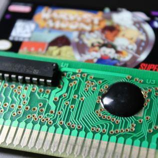 Detalhe da bolha de epóxi que protege o COB e do chip de desbloqueio que permite que o cartucho pirata rode em um SNES travado