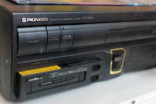O enorme Pioneer LaserActive (1993) rodava filmes e jogos usando LaserDisc, músicas com CDs e, com o módulo visto na foto, games de Mega Drive, além de jogos do TruboGrafx-16 e karaokê